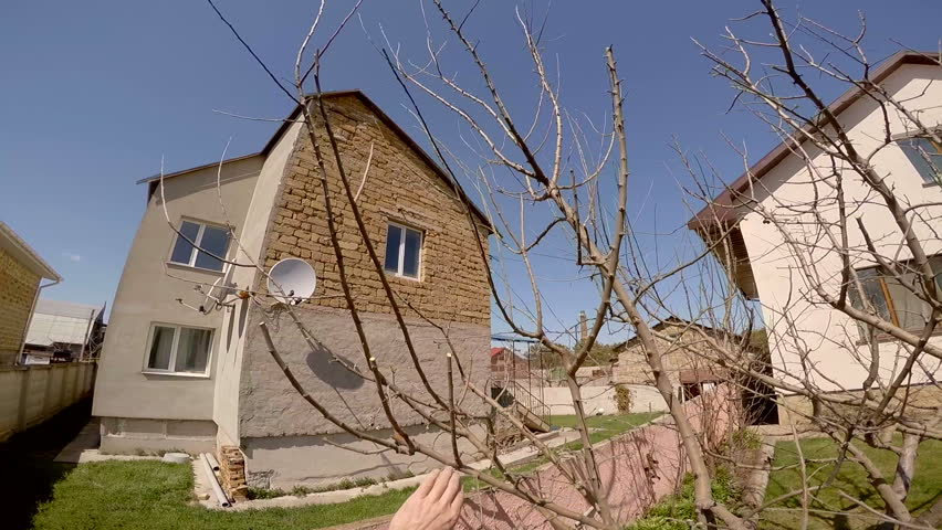 The shot from head point of view: a person is cutting tree branches with help of secateurs in the garden with houses and blue sky on background.  - HD stock video clip