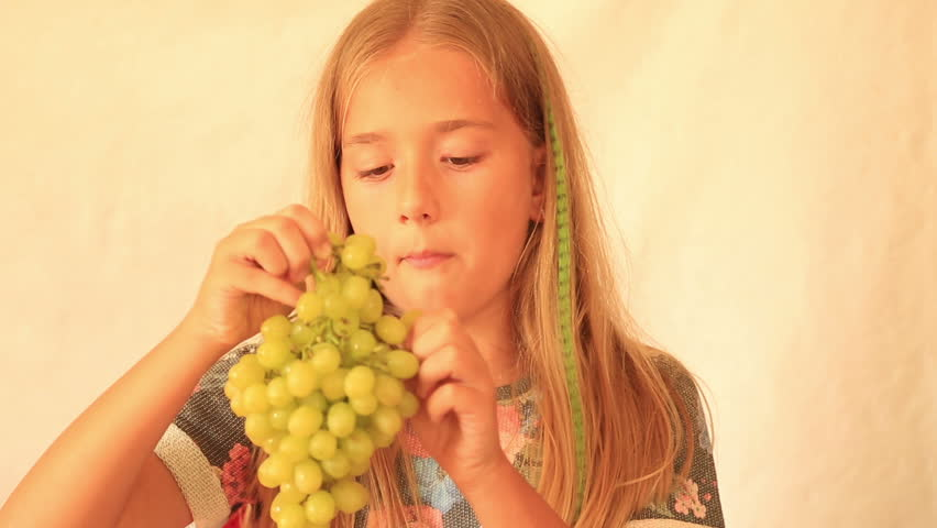 Cute girl eating grape