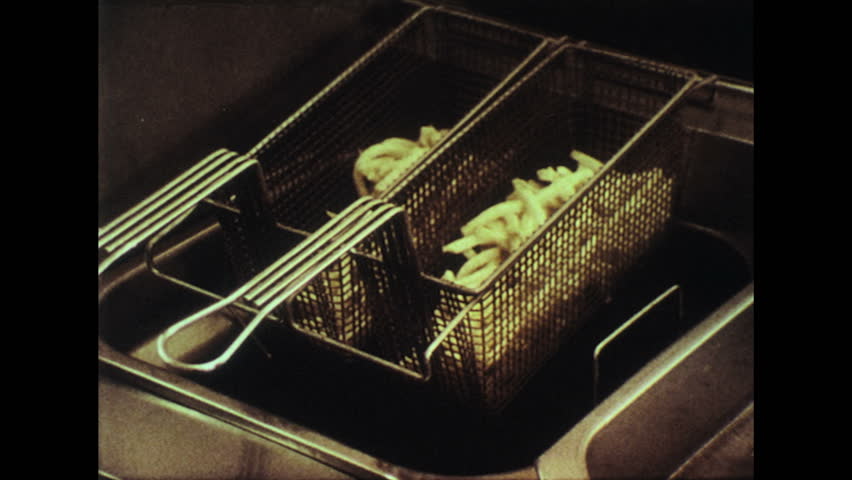 UNITED STATES 1970s – Cut potatoes are deep fried in oil to make french fries. - HD stock footage clip