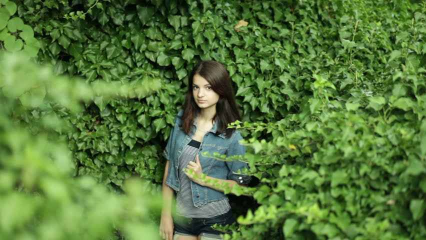 young dark-haired woman in the background of green plants - HD stock video clip