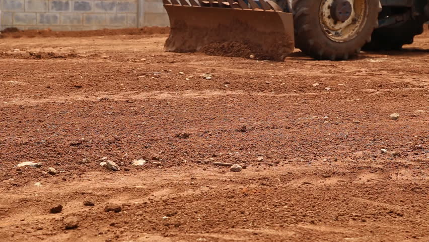 Tractor plows a red soil - HD stock footage clip