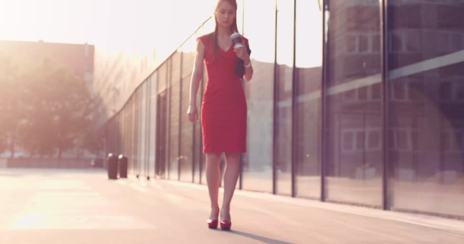 Woman walking in red high heeled shoes and stopping to massage her tired leg. Slow motion, 4K. Sexy legs in red high heels walking in city urban street. Cinematic shot.