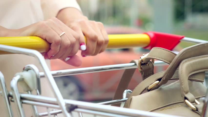 Woman  hands takeing shopping cart at street