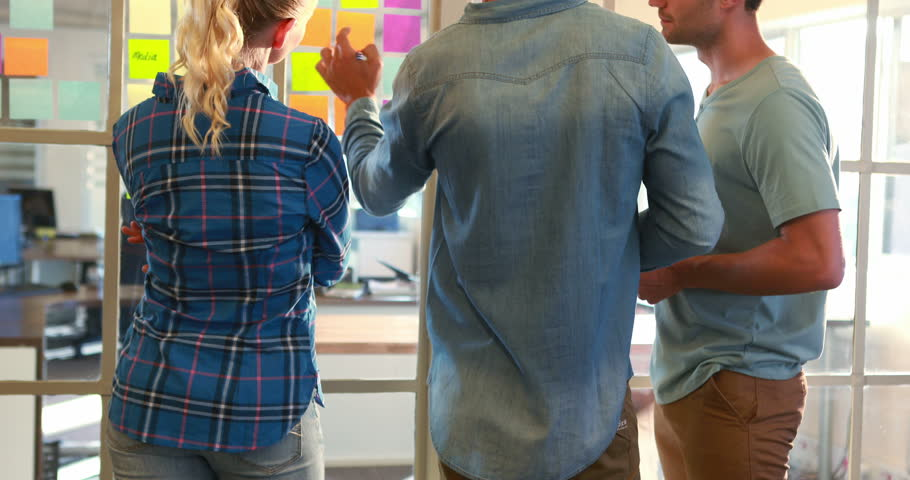 Casual business team looking at post it on the wall in 4k video - 4K stock video clip