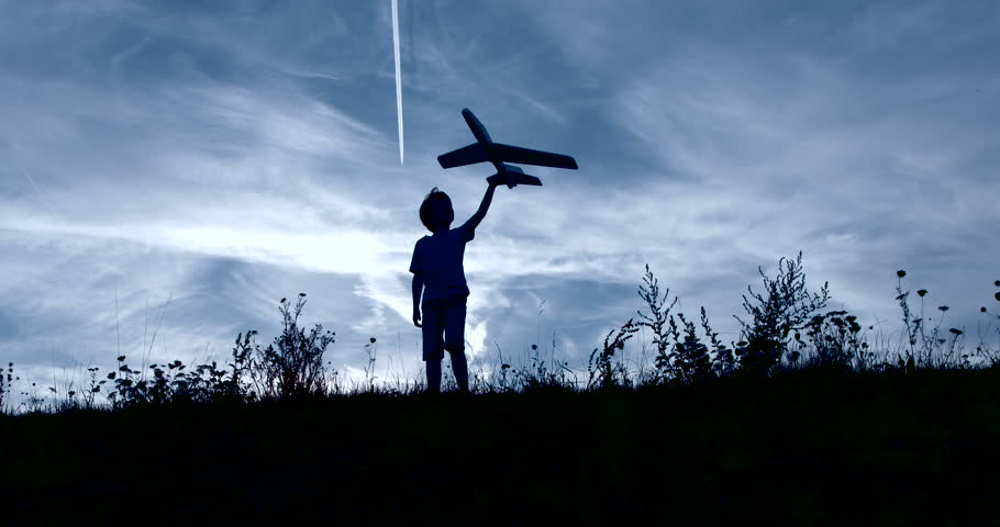 Boy playing outside with toy airplane silhouetted slow motion | Shutterstock HD Video #11460377