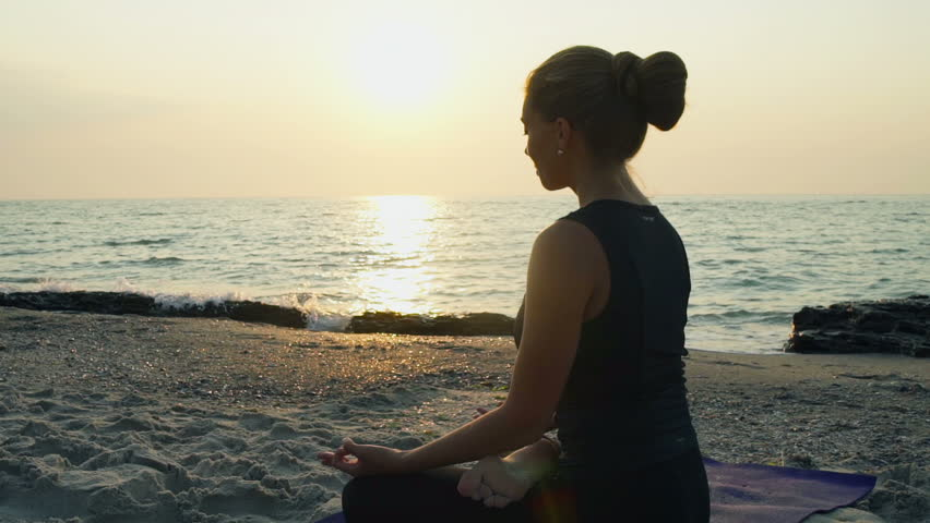 Young female meditates on the beach slow motion | Shutterstock HD Video #11479574