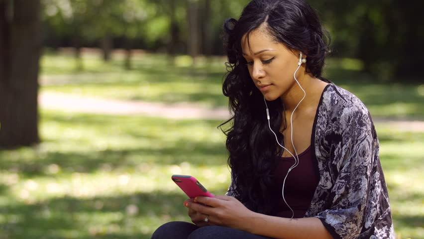 A woman sitting in a park texting with headphones