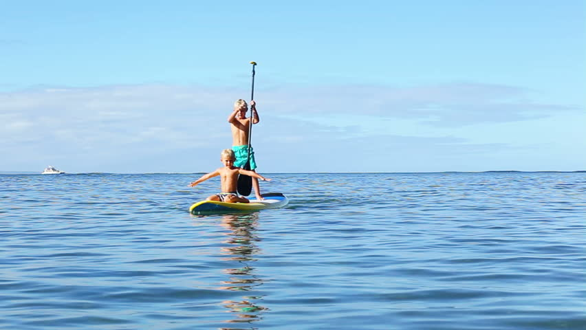 Stand Up Paddling. Two Cute Young Blonde Boys Learning to Surf. Summer Fun Family Vacation Healthy Lifestyle. Tandem SUP. | Shutterstock HD Video #11541701