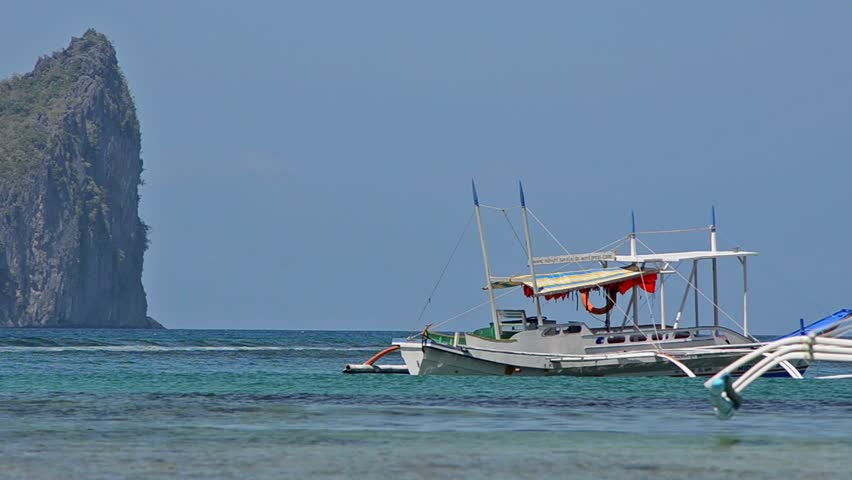 Philippine fishing boat and sea rocks on background in El Nido, Palawan island, Philippines