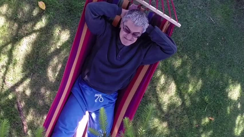 Caucasian middle-aged man with comical expression relaxing in hammock, aerial view.