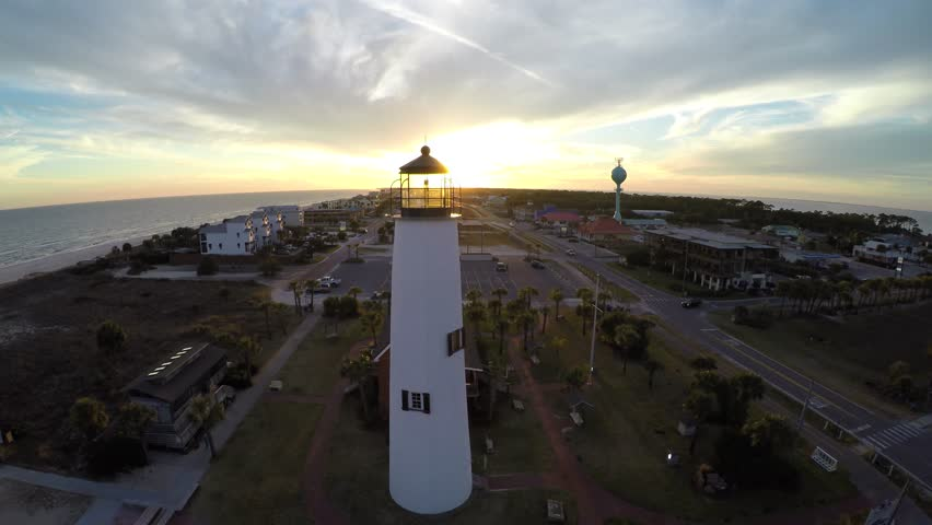Flying slide left past a lighthouse with sunset in the distance. - 4K stock video clip