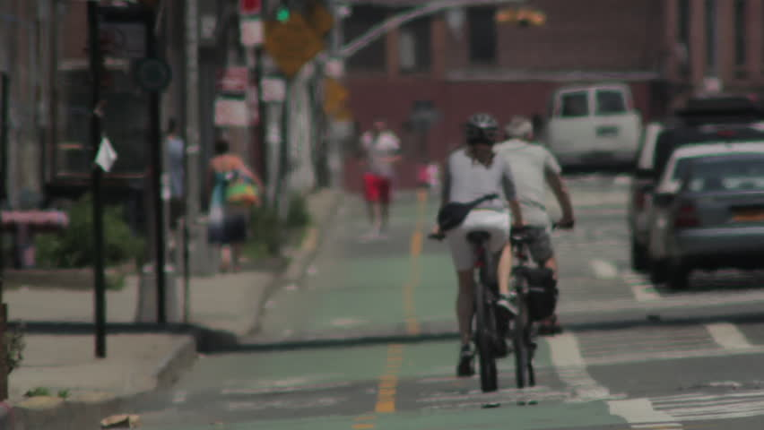 Biking in New York City. Couple rides bikes on a bike lane on a hot day with depth of field focus. | Shutterstock HD Video #11609732
