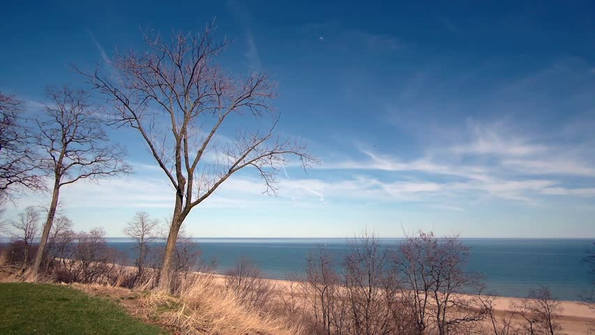 Time lapse on a sunny day of Lake Michigan Beach.  View from a lookout of the beach, water, and surrounding trees and grass. - HD stock footage clip