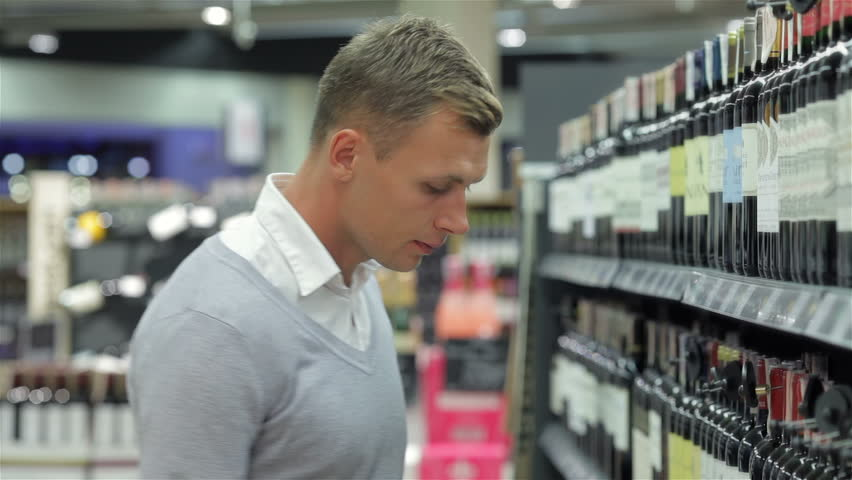 Portrait of mid adult man showing alcohol bottle while standing by shelves. Young male shopper looking at liquor bottle at supermarket.