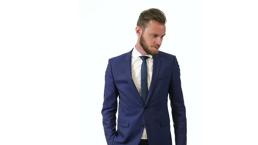 Attractive businessman wearing a blue suit and tie, standing against a white background, HD video. - HD stock video clip