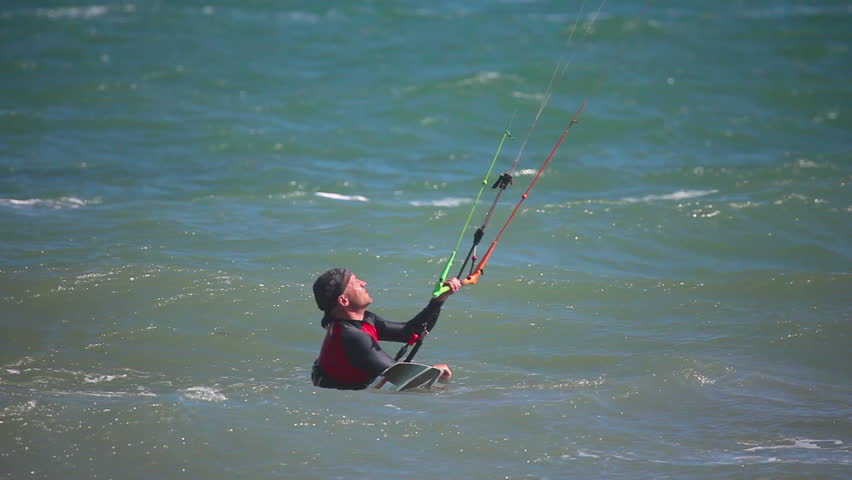 MUI NE, VIETNAM - JANUARY 31, 2014: Unidentified kitesurfer surfing on the waves with the kite at Mui Ne resort beach on January 31, 2014 in Mui Ne resort, Vietnam.   Shutterstock HD Video #11671472