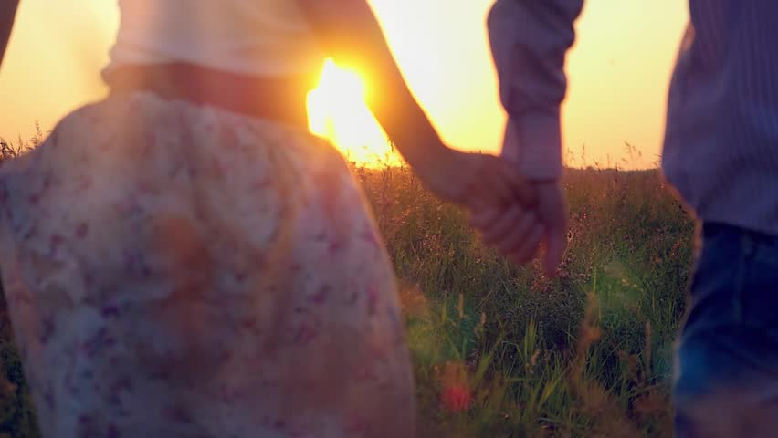 Slowmotion of Fashionable happy couple join hands runs across the field in sunset light and cuddling, lifestyle - happiness. 1920x1080 - HD stock footage clip