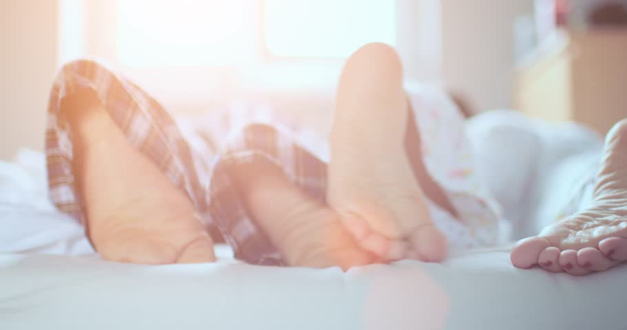 Couple is jumping into bed, close up on feet. Slow Motion 120 fps, 4K, DCi. Young man and woman having fun getting to bed. Healthy love life and relaxation. Lens Flare.