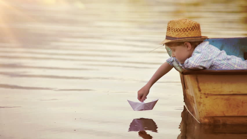 Little boy sitting in the real boat sets his paper ship off to sail