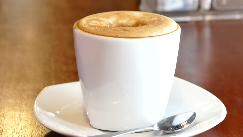 Putting sugar and mixing with a spoon the cappuccino  | Shutterstock HD Video #11812349