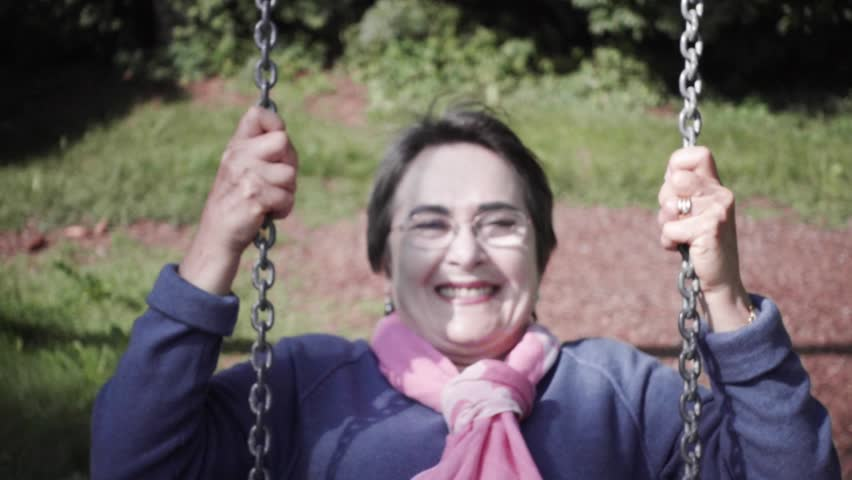 Portrait of senior woman on a swing of the retirement place. Slow motion