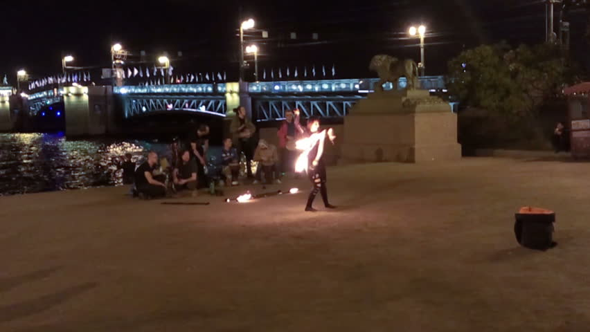 ST. PETERSBURG, RUSSIA - CIRCA SEP, 2015: Woman makes fireshow on Admiralty bank near Palace Bridge at night. People wait drawbridge opening. Traditional rise of bridges at Neva river - HD stock footage clip