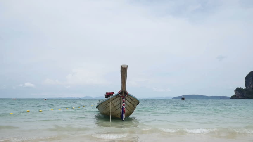 Traditional wooden thai longtail boat at the beautiful tropical beach. Railay beach, Krabi, Thailand. - HD stock footage clip