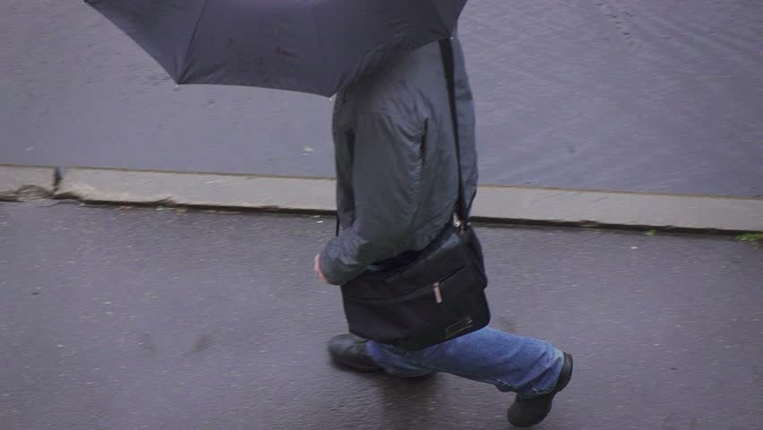 Rainy day in city streets, water drops, puddles, man walking under umbrella, slow motion, overhead view. | Shutterstock HD Video #11919791