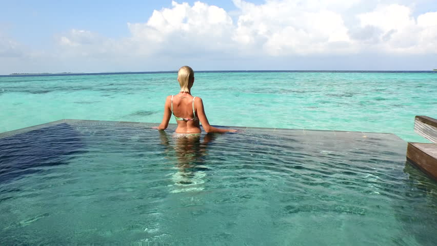 AERIAL: Young woman in bikini standing at the edge of the pool in ocean front villa pool and looking towards the sea horizon - 4K stock video clip