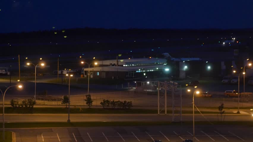 An airport at night with bright lights and airplanes landing and taking off on the runway