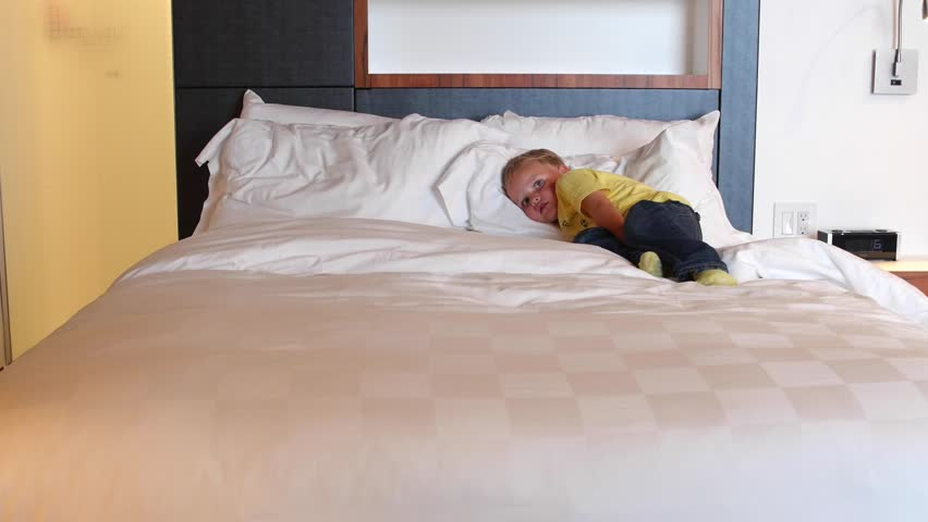 A toddler boy lying on a big comfortable king size bed in a hotel room #11926397