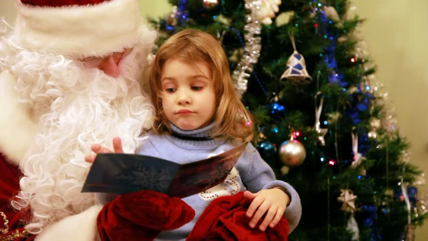 beautiful girl reads in Santa Claus kneeling in front of the tree - HD stock footage clip