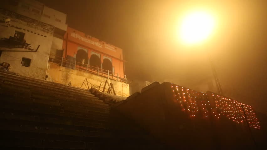 VARANASI, INDIA - 20 FEBRUARY 2015: View on foggy street and stairs in Varanasi in night time.