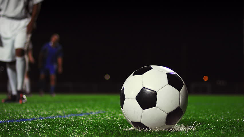 Close up of a soccer ball being kicked in slow motion at night - 4K stock video clip
