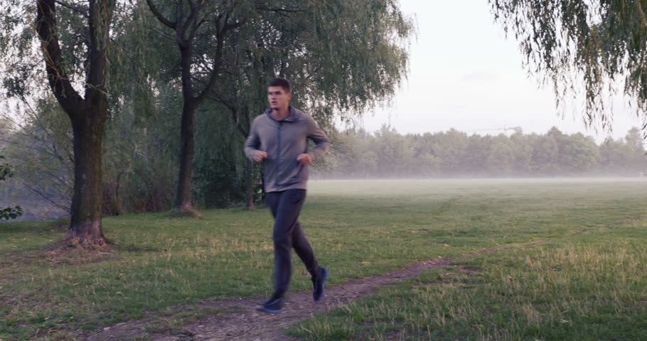 Young man running at foggy morning in park - 4K stock video clip