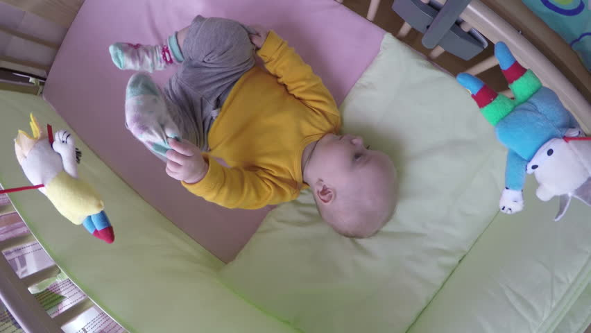 playful little baby girl having fun with toy carousel in bed. 4K UHD wide angle shot. Camera hang on carousel handle.
