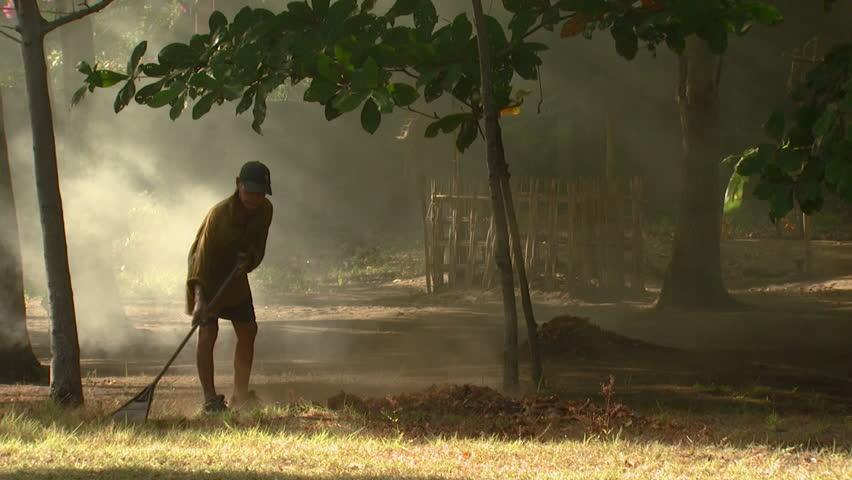 Bali, Indonesia - October, 2012: Wide shot of old man raking leaves - HD stock video clip