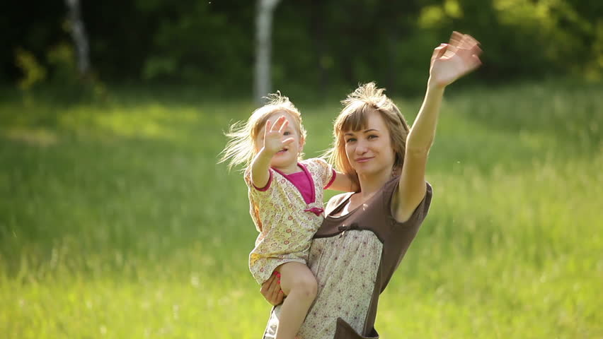 Happy mother and child waving hands in the park  - HD stock footage clip