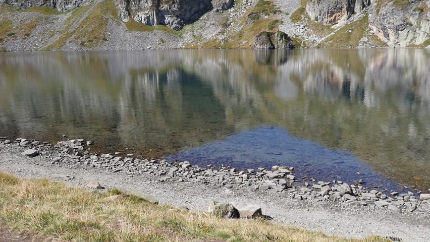 NATIONAL PARK RILA, BULGARIA - SEP 19, 2015 - Clear pure water and shore of Rila Lake in a National Nature Park in Bulgaria | Shutterstock HD Video #11993492