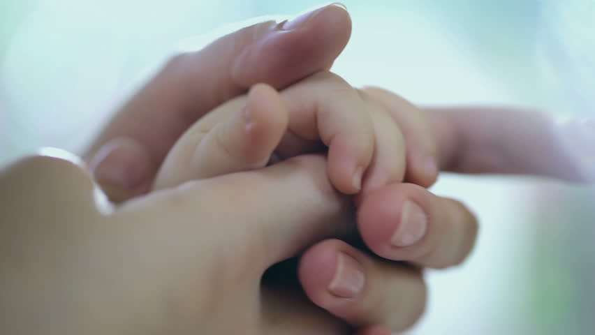 Caring mother with baby, Concept of love and family. hands of mother and baby closeup, Hand in hand. Mother care. Playing with baby at home. Slow Motion.FEW SHOTS !