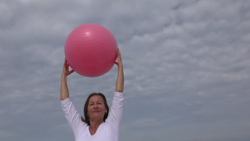 Portrait attractive active mature woman stretch exercising at ocean beach with pink fitness ball to keep healthy and fit, sea, horizon and sky as outdoor - 4K stock footage clip