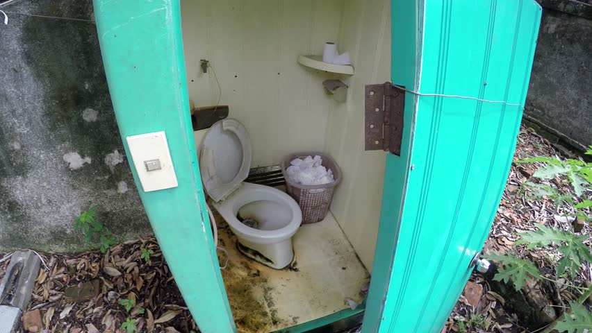 Broken dirty outside toilet water floating all out of the pot and over the ground outside lavatory light green neon doors and showing toilet paper in trash bin in the corner of the small structure 4k