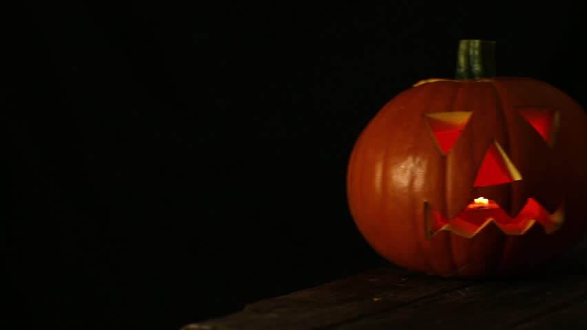 Scary Halloween Pumpkins carved with a face and glowing in the dark | Shutterstock HD Video #12029411
