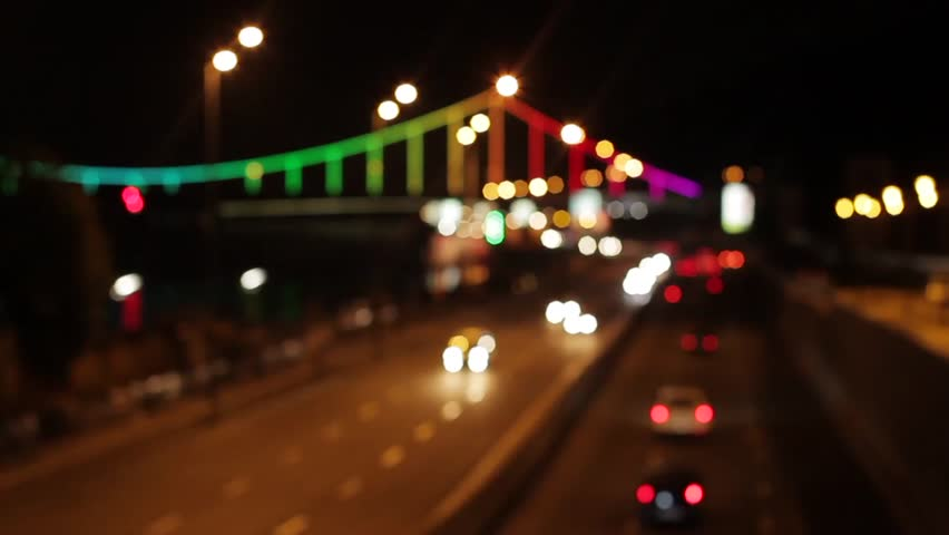 Blurring background of an evening city. View from the bridge on the evening city. Bridge in colorful lights. A shot for a background.