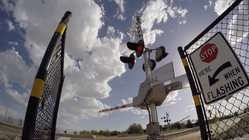 Wide view shot of railroad crossing as arms go down and come back up on a crisp Summer afternoon with white clouds passing overhead. - HD stock footage clip