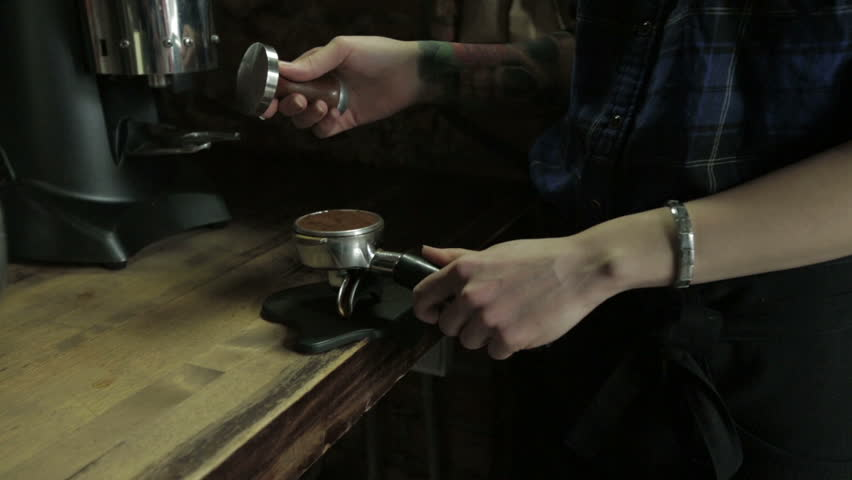Barista tamping the grind coffee for espresso, close-up - HD stock footage clip
