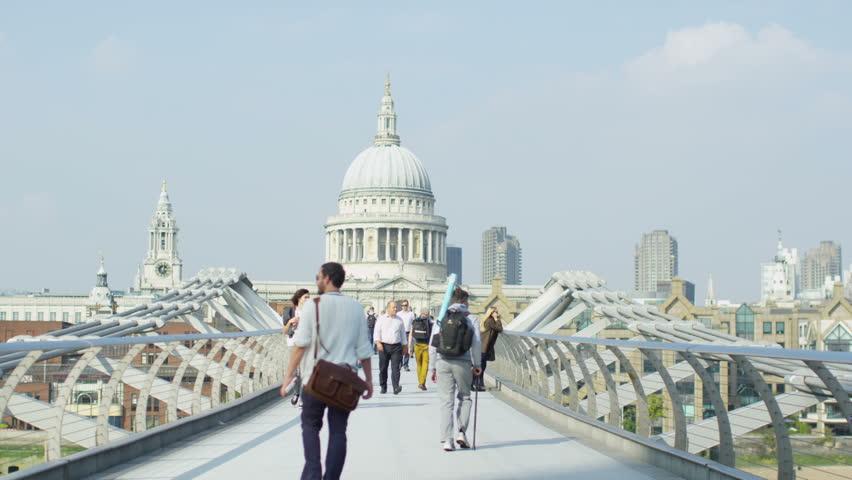 LONDON SEPTEMBER 2014 - Crowd of people crossing the Millennium footbridge.  The bridge was originally nicknamed the wobbly bridge due to it's swaying motion. LONDON, UK 11 SEPTEMBER 2014 EDITORIAL - 4K stock video clip