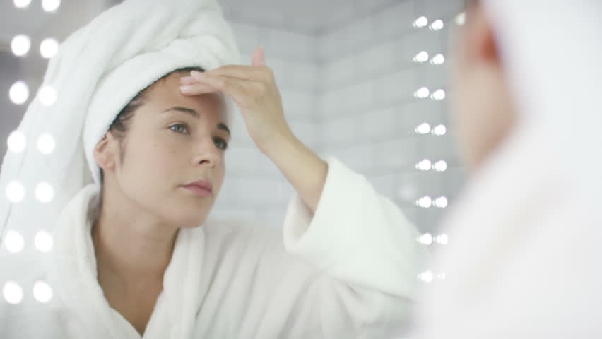 4K Attractive woman moisturising in the bathroom mirror, shot on Red Epic Dragon