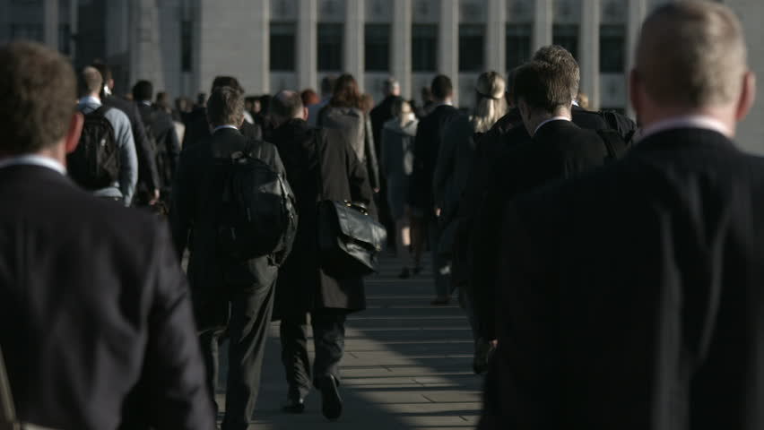 Slow motion of a large crowd of anonymous people in front of grey building in 4K. Large crowd of commuters and pedestrians walk across London Bridge to the City of London on a sunny morning.