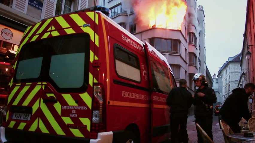 Firefighters running to control a huge fire. 4 OCTOBER 2015 - PARIS, FRANCE; An apartment explodes and catches fire, breaking all the windows and killing one person.